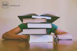 Frau sitzt hinter einem Stapel Lehrbücher, von der nur die auf dem Tisch abgestützten Ellbogen zu sehen sind - zuerst Theorie, dann Praxis.