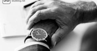 Eine Männerhand legt sich um das andere Handgelenk, um auf die Armbanduhr schauen zu können - Überstunden machen.