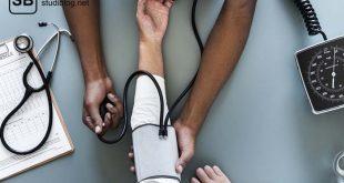Mann misst den Blutdruck einer Frau, daneben liegt ein Stethoskop - Untersuchungskurs im Medizinstudium.