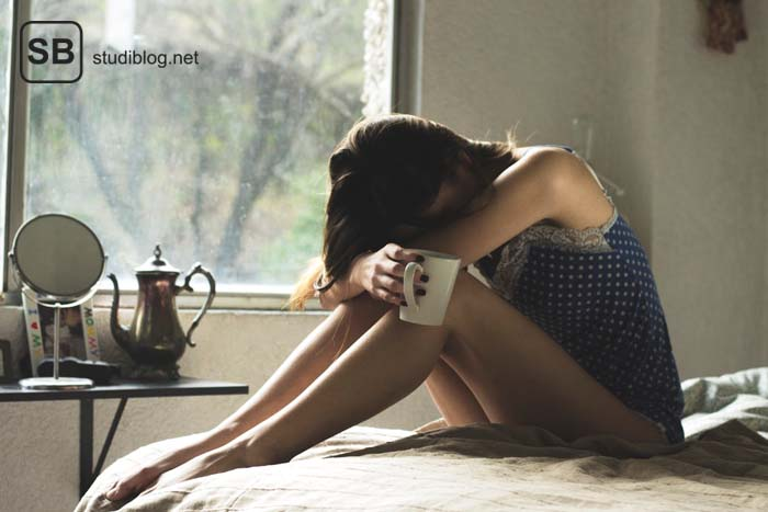Angst vor dem Versagen im Studium: Junge Frau sitzt in Schlafklamotten auf dem Bett, hat die Beine angezogen und vergräbt den Kopf auf den Knien mit einer Kaffeetasse in der Hand.