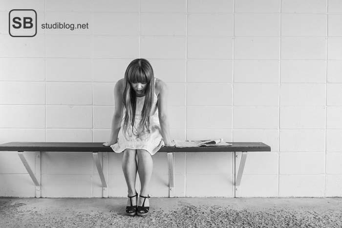 Junge Frau sitzt besorgt auf einer Bank in der U-Bahn - Wartezeit fürs Medizinstudium.