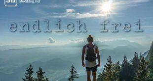 Ein Student mit Rucksack auf dem Rücken auf einem Berg mit toller Aussicht und strahlendem Sonnenschein