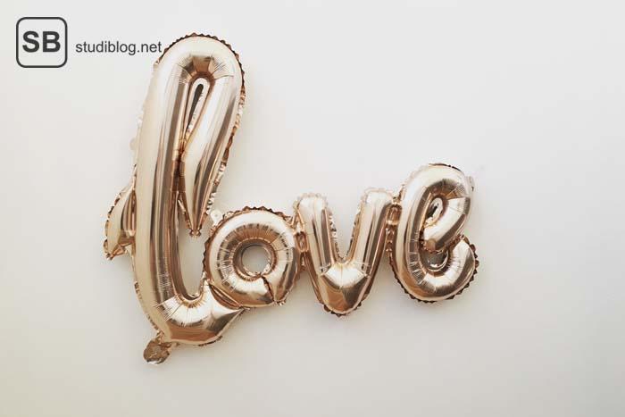 Rosegoldene Luftballonbuchstaben, die das Wort 'love' darstellen - Lektionen über die Liebe aus meinen Zwanzigern.