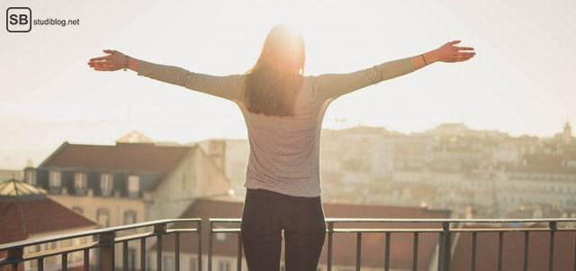 Richtig Pause machen: Frau steht auf Balkon und streckt ihre Arme von sich