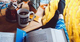 Student liegt mit Buch auf der Couch beim Lernen mit der Frage ob Karteikarten oder Zusammenfassung