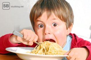 Kinder das sich einen Haufen Nudeln ins Gesicht schiebt zum Thema Knigge, mehr Schein als Sein?