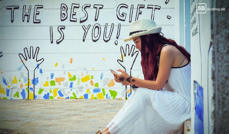 Eine Ode an die Akzeptanz: Mädchen sitzt vor dem Spruch an einer Wand: The best gift is you!