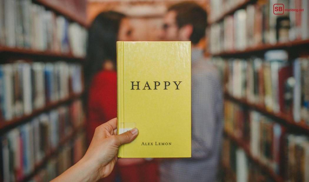Happiness-Ratgeber: Jemand hält ein Buch mit der Aufschrift Happy vor ein Pärchen, das in einer Bibliothek steht