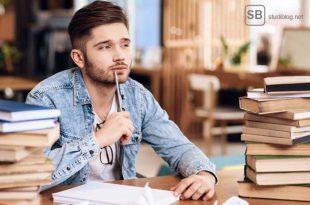 Student sitzt nachdenklich am Schreibtisch zum Thema Kosten im Studium