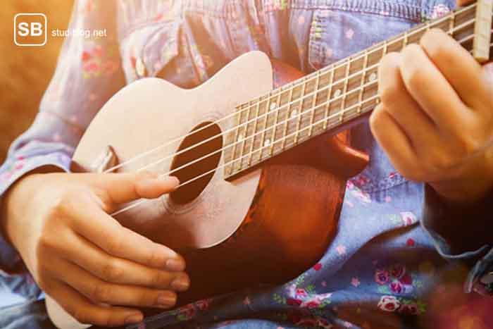 Mädchen das Ukulele spielt und damit richtig glücklich ist