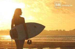 Studenten mit Surfbrett an einem Strand bei Sonnenuntergang zum Thema Erholung in den Semesterferien