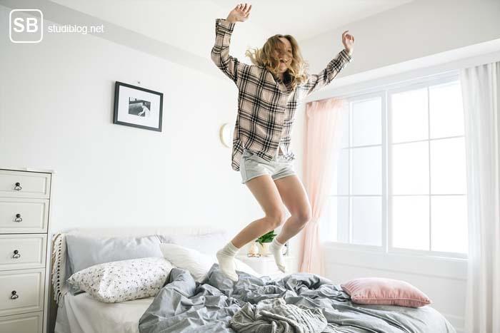 Erste eigene Wohnung - Studentin springt auf ihrem Bett herum