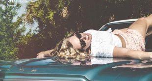 Studentenkredit - Studentin liegt auf der Motorhaube eines Mustangs