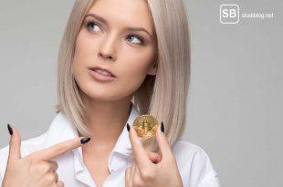 Studentin mit einem Bitcon in der Hand zum Thema Kryptowährung