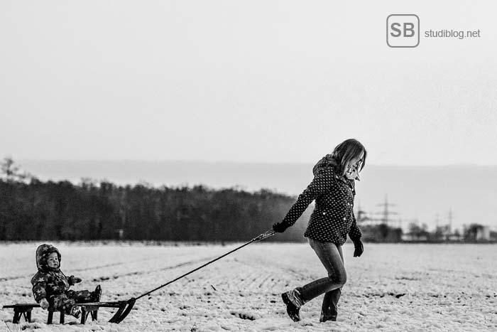 Studieren mit Kind - Mutter zieht Kind mit Schlitten durch den Schnee