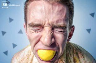 Student beißt in Zitrone zum Thema nicht den Humor verlieren beim Schreiben einer Studienarbeit