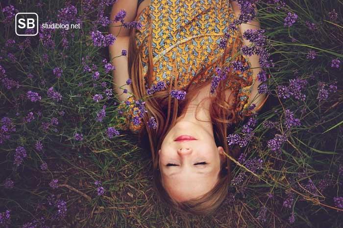 Studentin liegt im Gras zum Thema Aufstehen - so wirst Du zum Frühaufsteher