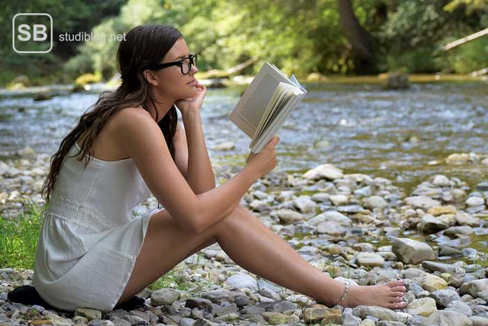 Urlaubssemester, Studentin sitzt mit Buch an einem Fluss